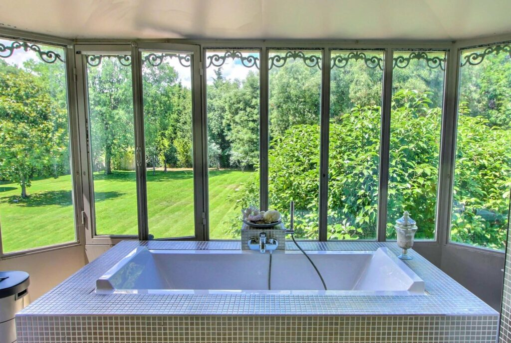 bathroom with large bath tub and floor to ceiling windows with view of garden