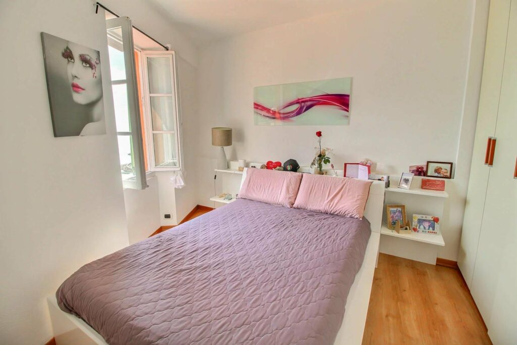 bedroom with purple and pink bedding and french door windows with sea view
