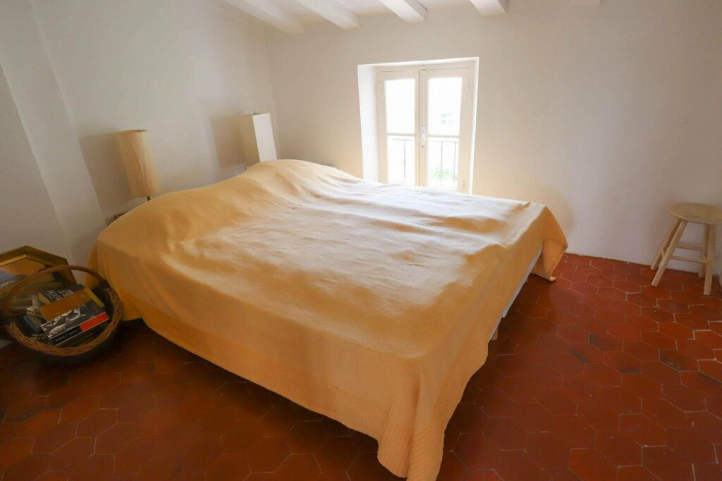 bedroom with queen size bed in center covered with yellow sheet and white walls