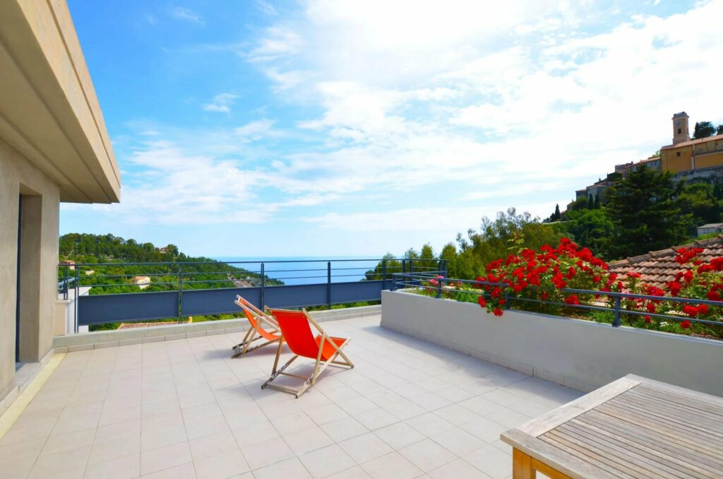 terrace with exceptional mediterranean sea and mountain view with red chairs