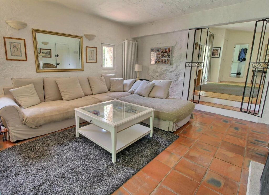 white sofa in living room with white center table with glass top and grey rug beneath