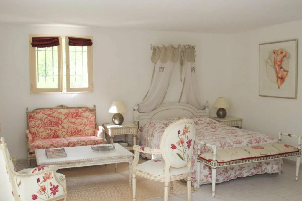 classic french style bedroom with white pink colored accents on bedding and chair