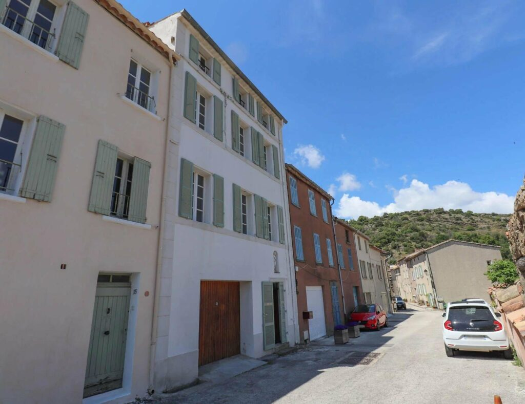south of france apartment buildings white exterior and blue shutters on angled hill