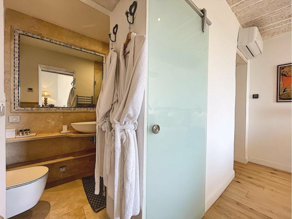 large bathroom with stone tile and sliding glass door