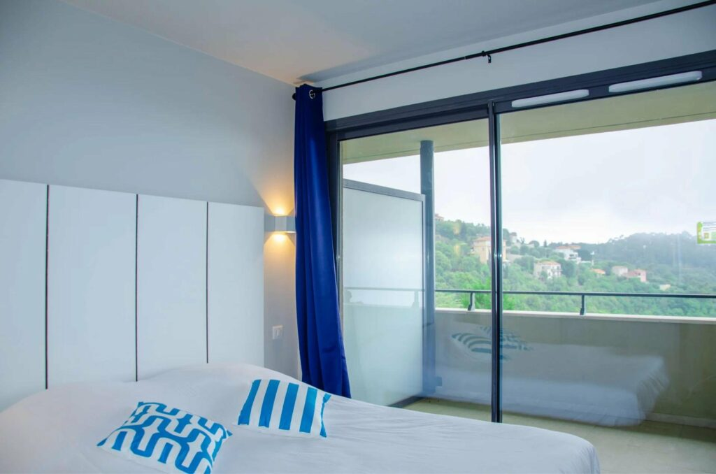 bedroom of property in south france with sliding glass door access to terrace with sea view