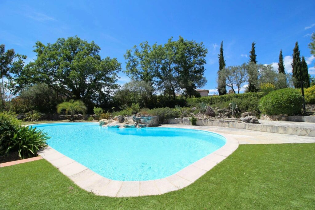 backyard large pool of villa in southern france with tall trees surrounding it