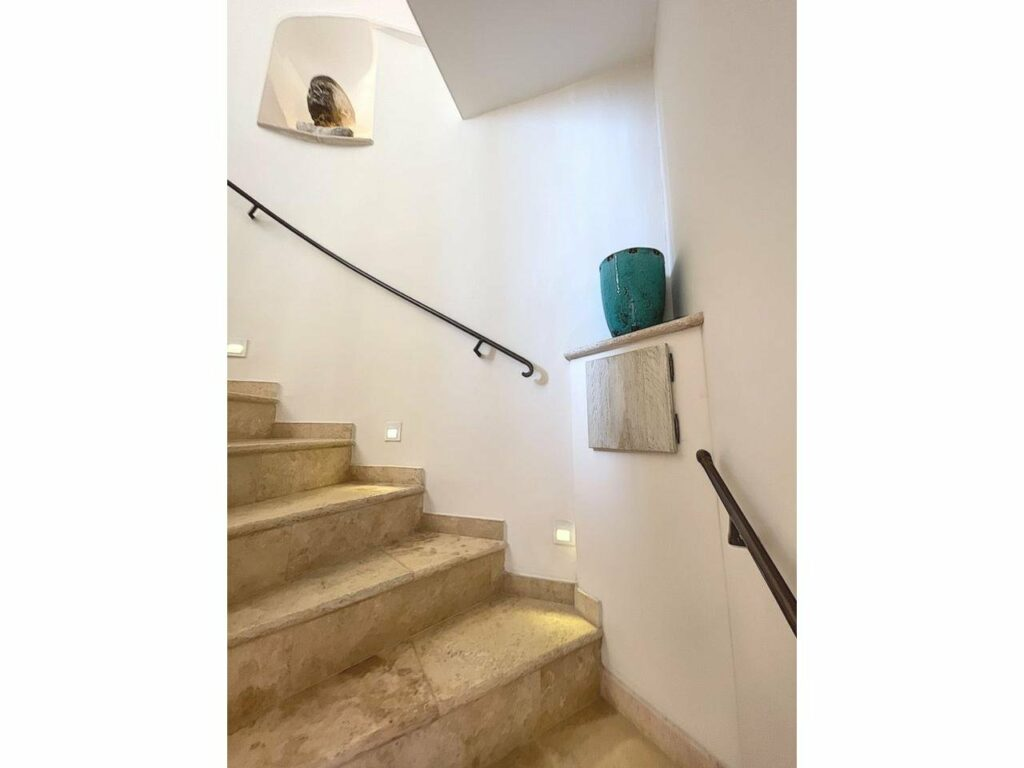 stairway with cream colored tile floors and metal railing on white wall