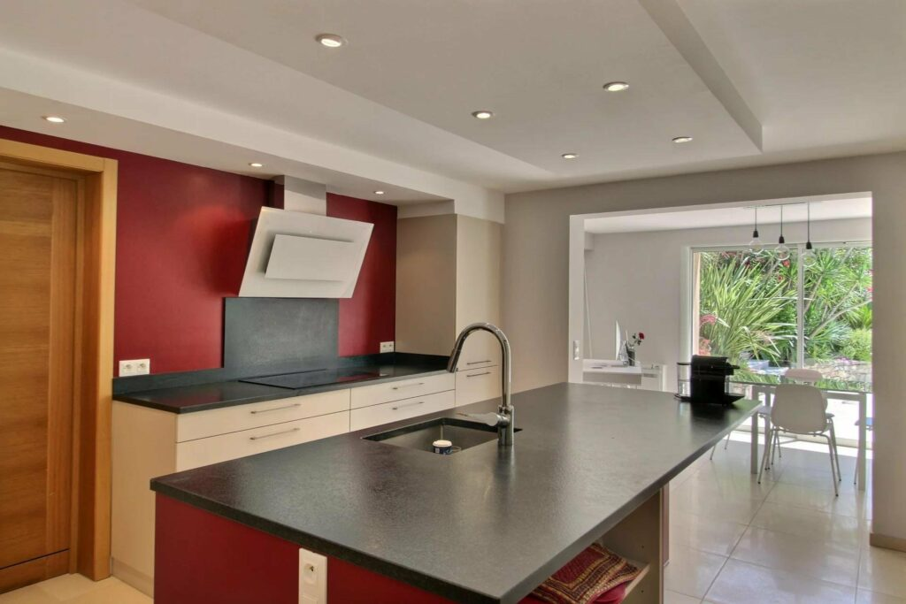 kitchen with dark stone island and red walls
