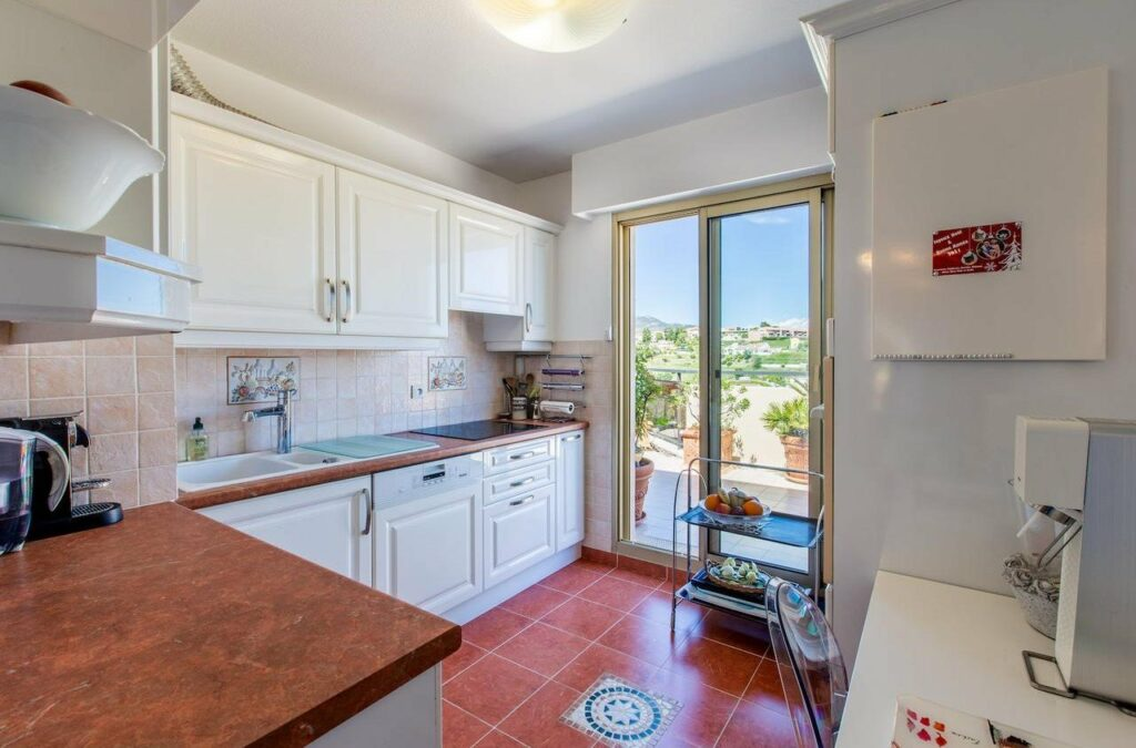 kitchen with red tile floors and white cabinets and wood counter tops sliding door with sea view
