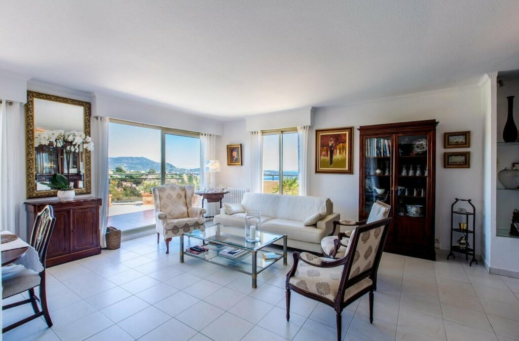 modern chic living room of apartment for sale in nice with balcony access and white tile floors