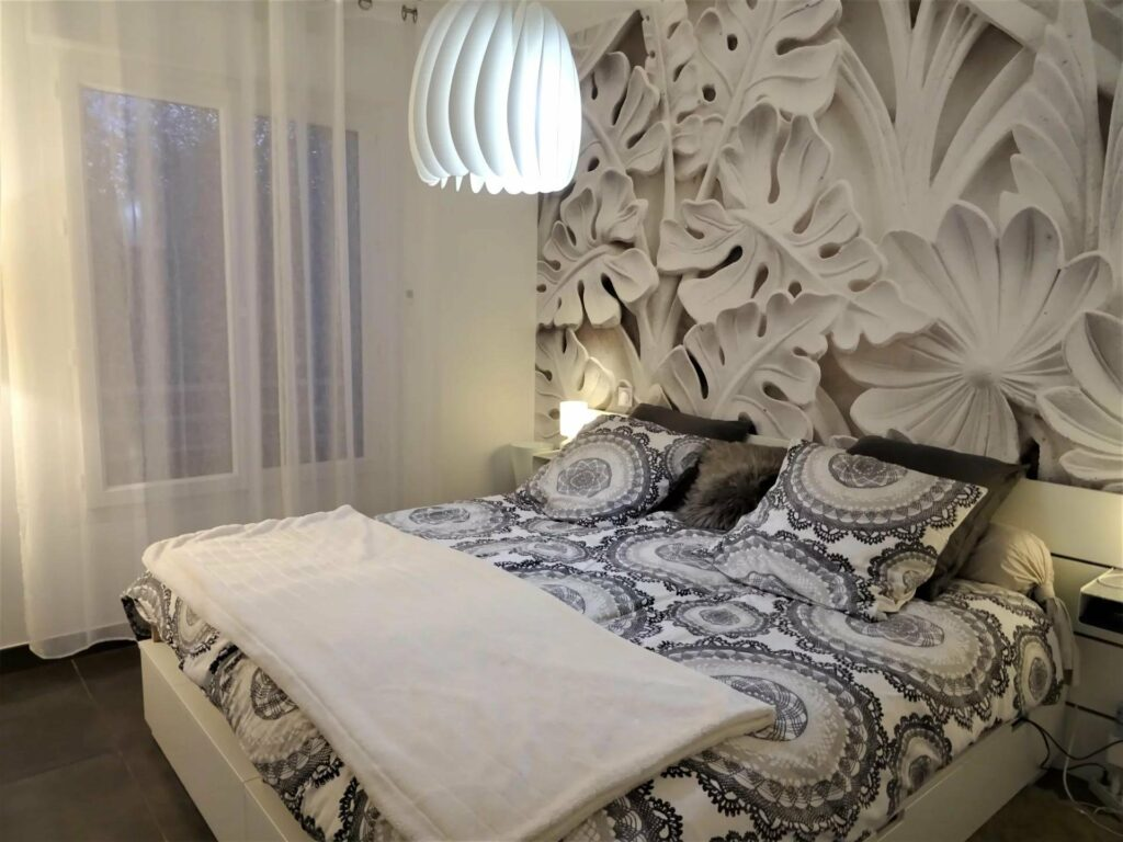bedroom of property south france with printed black and white wallpaper