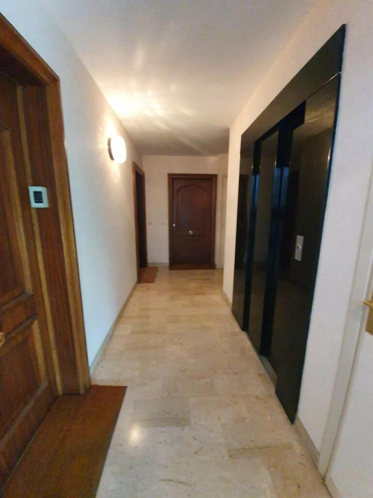 outside of apartment with large wood doors and tile floors throughout the building