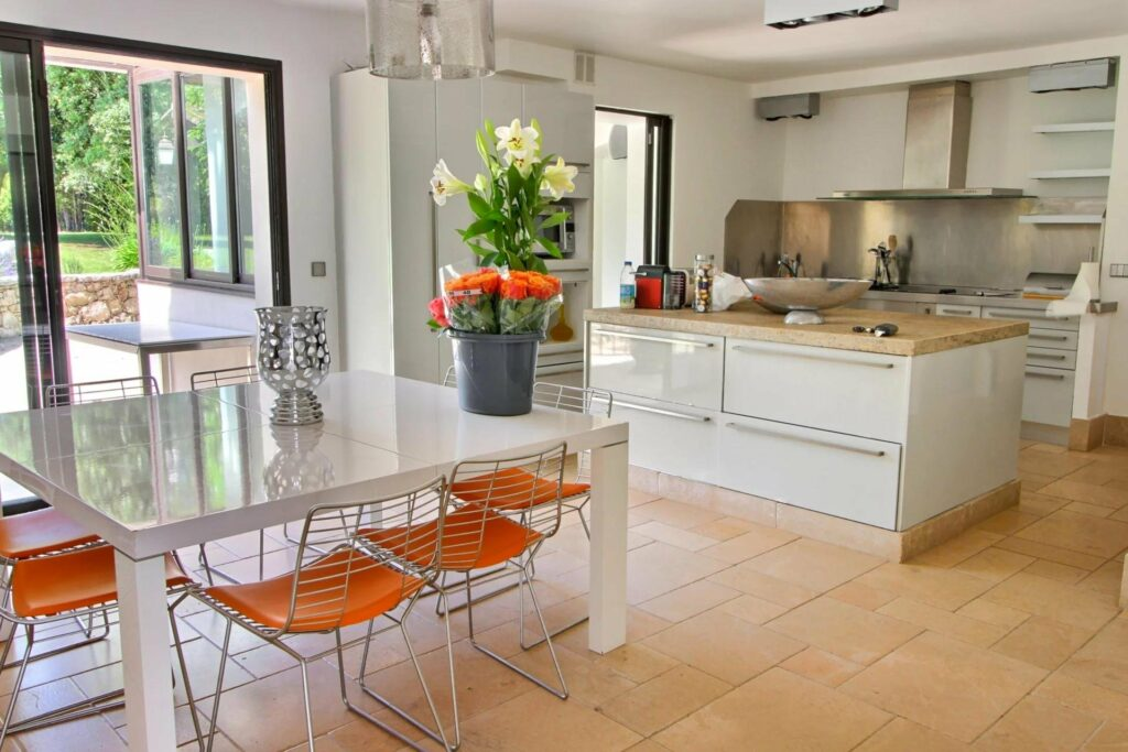 bright kitchen with white table and orange metal chairs with flowers on top in south france luxury villa
