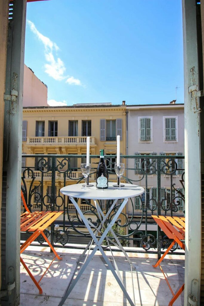 balcony facing street with white table and orange chairs