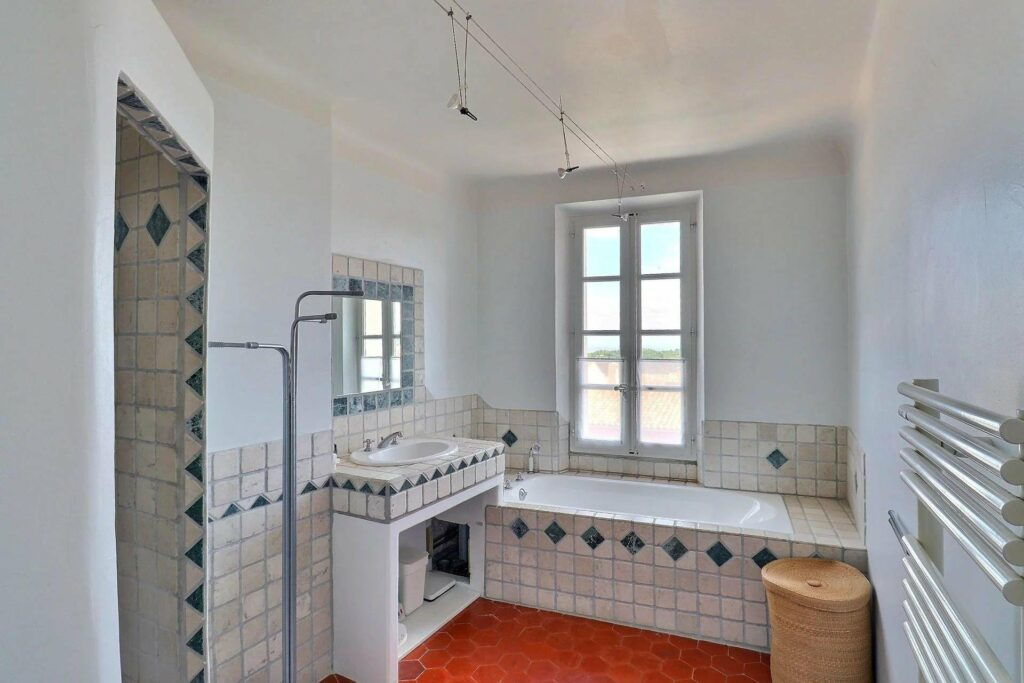 bathroom with tile floors blue toned with french windows