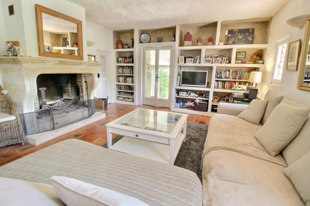 living roof at provence villa with white couch facing white fireplace surrounded by shelves with books