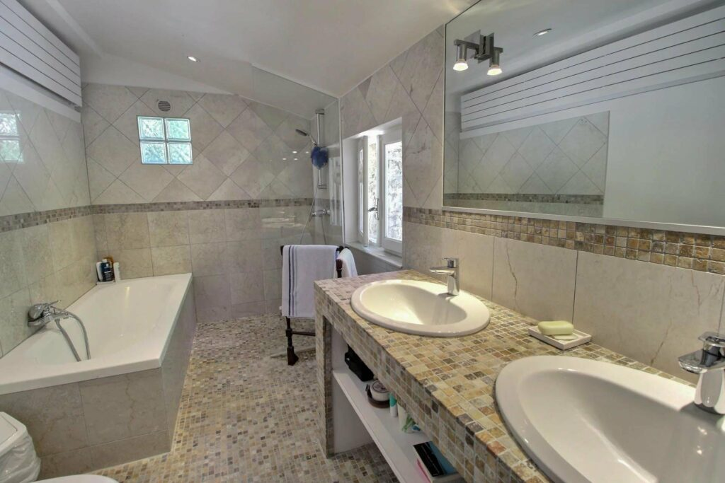 bathroom with double sink and large mirror facing white bath tub
