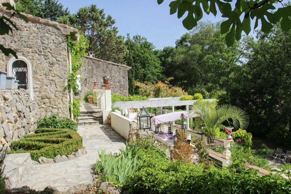 backyard with green plants around and exterior of villa with stone walls