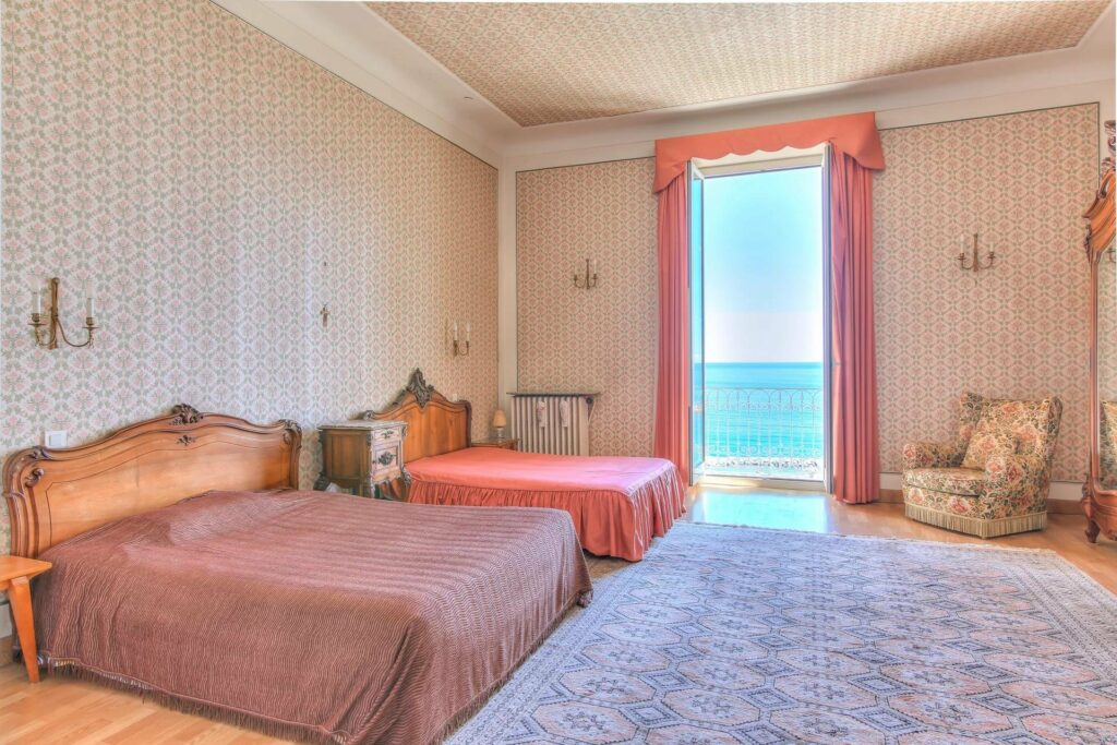 large open bedroom with floor to ceiling window that has a sea view south