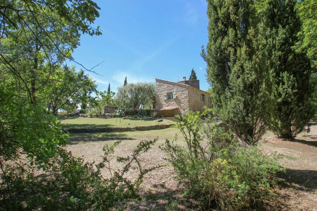 south of france property with large stone house surrounded by beautiful garden
