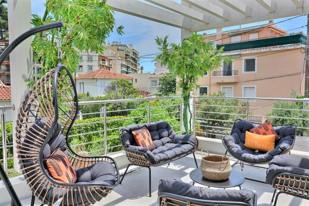 terrace of property for sale in the south france with a garden view and retro outdoor furniture