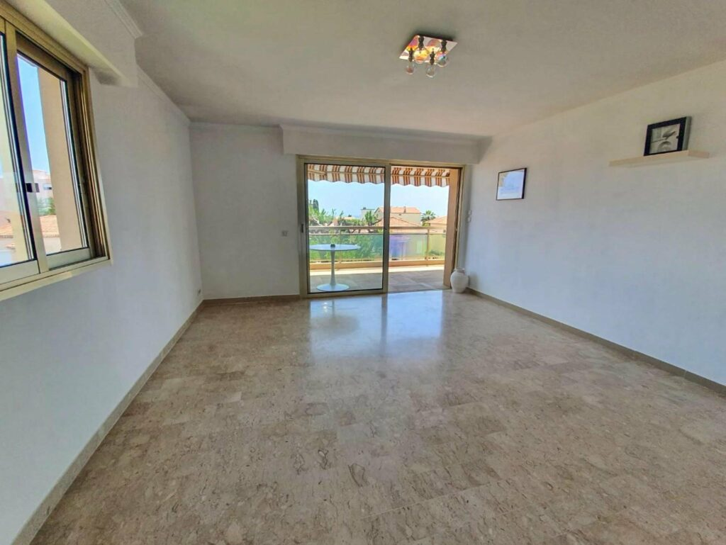large open living room in apartment with sliding door access to balcony
