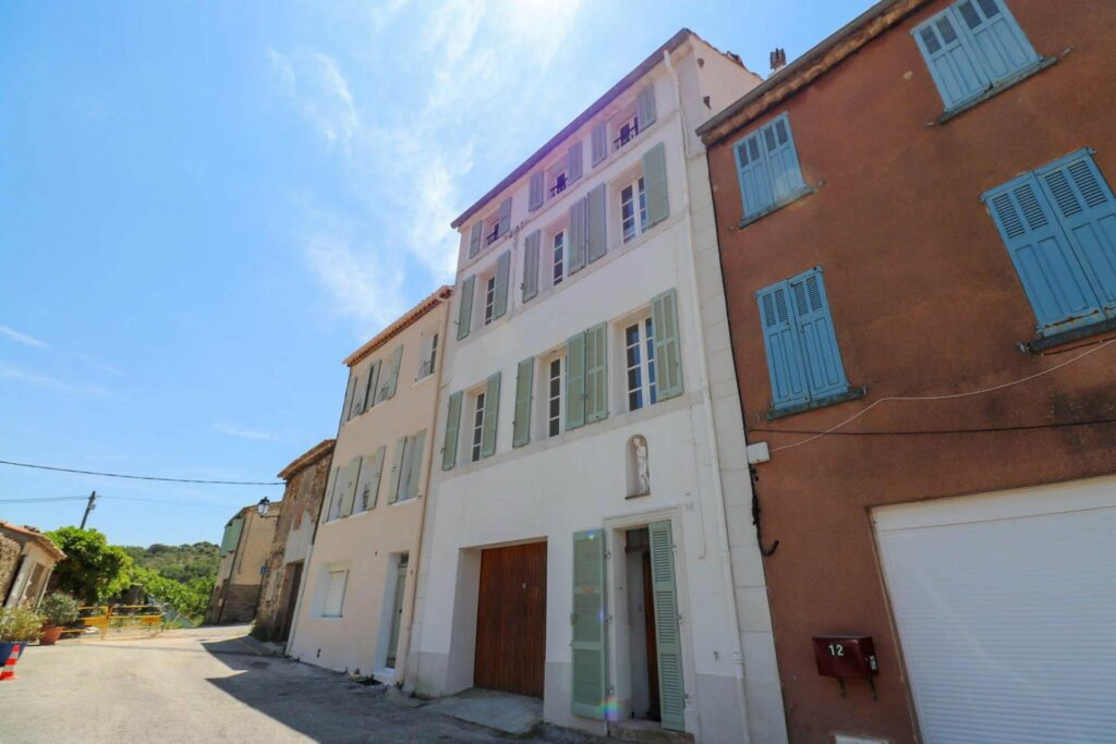 exterior french apartment buildings with cream walls and blue shutters and doors on hill