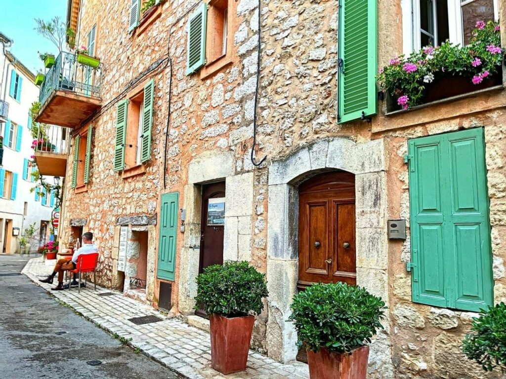 properties in village in south of france with stone exterior and large wooden door and bright blue shutters
