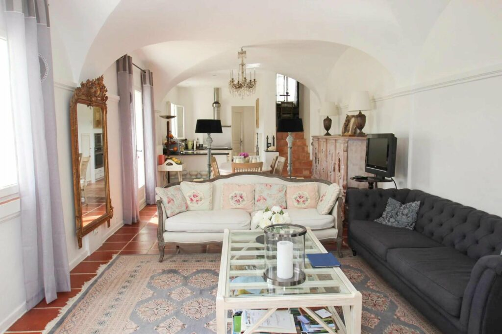 living room classic french style with large printed rug and cream colored couch
