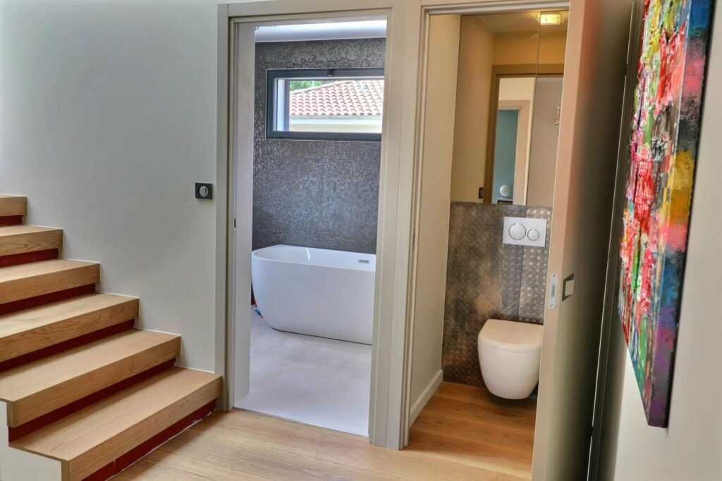 modern bathroom with white bath tub and seperate toilet room