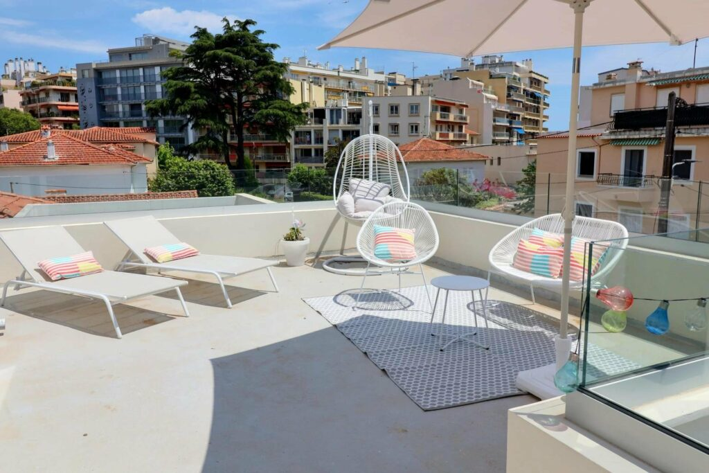terrace of apartment with view of buildings and white outdoor furniture