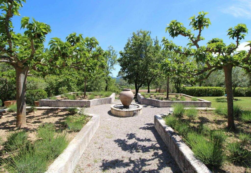 garden in south france with stone four path walk way with stone sculpture in center