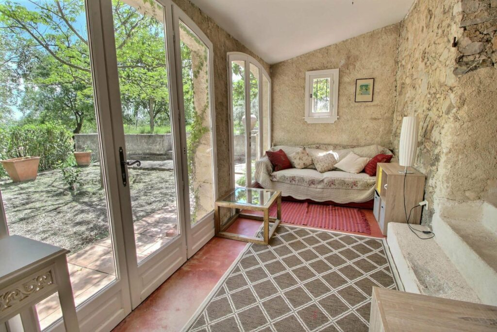 sitting area at french home with pattern rug on floor and large glass doors to provencal backyard