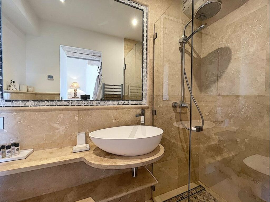 bathroom with white ceramic sink and standing shower
