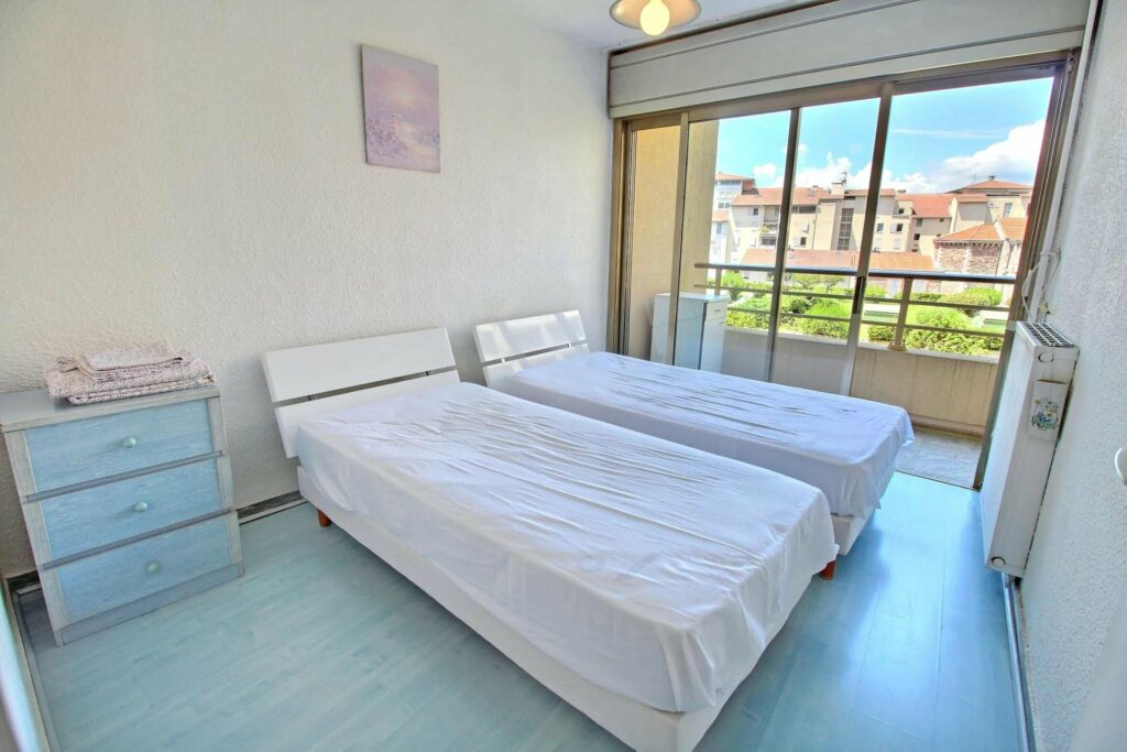 double single beds with white bedding next to terrace sliding door