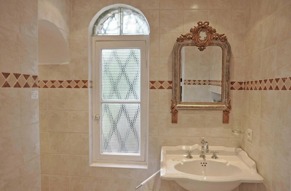 classic style bathroom with long window and tile design walls