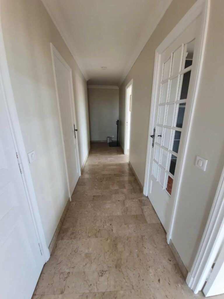 hallway with tile floors and white cabinets on both sides