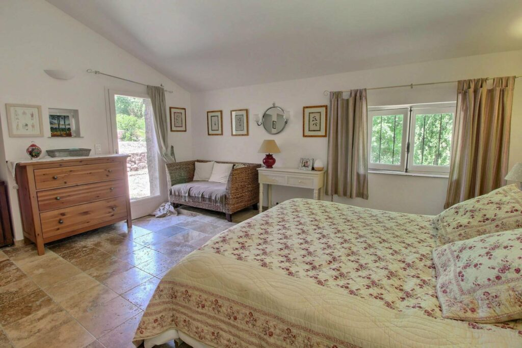 bedroom in provencal villa with large queen size bed and tile floors with access to backyard
