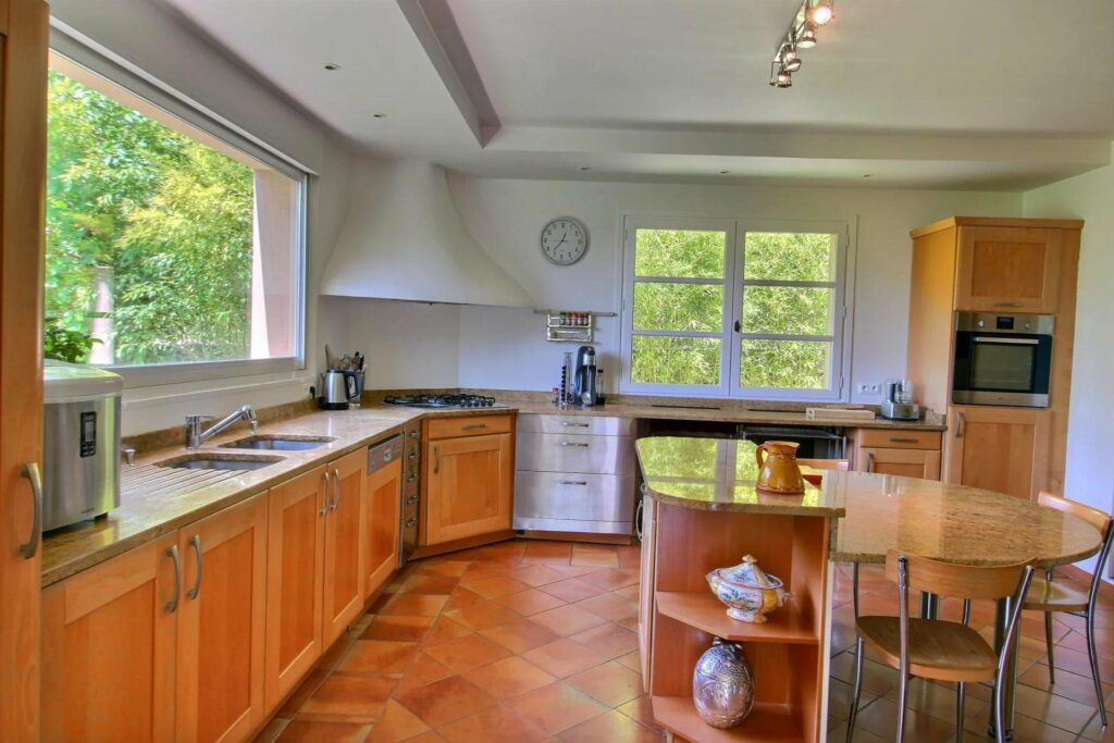 kitchen of property in opio with light wood floors and garden facing windows