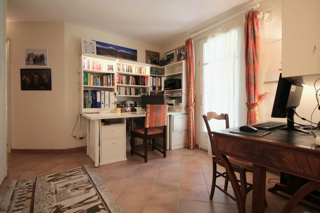 desk area of apartment in sotuh france with books filled with shelves and white square desk
