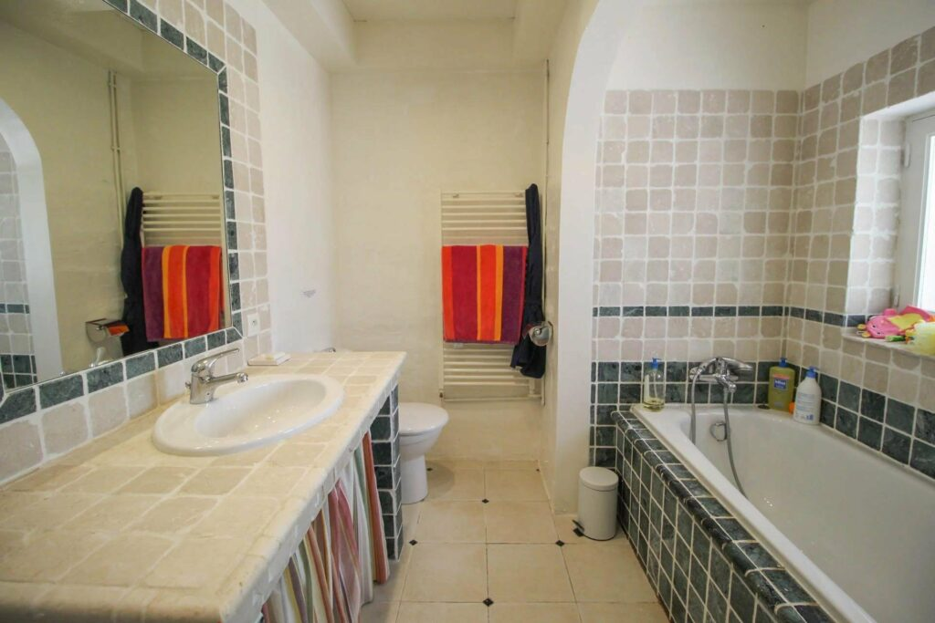 bathroom with pattern tile and and red accent towels in south france house