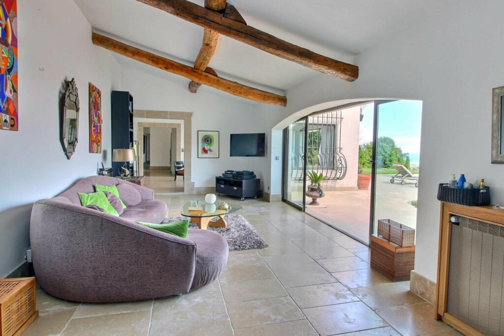 sitting room with exposed wood beams and purple couch facing large glass doors with view of south france