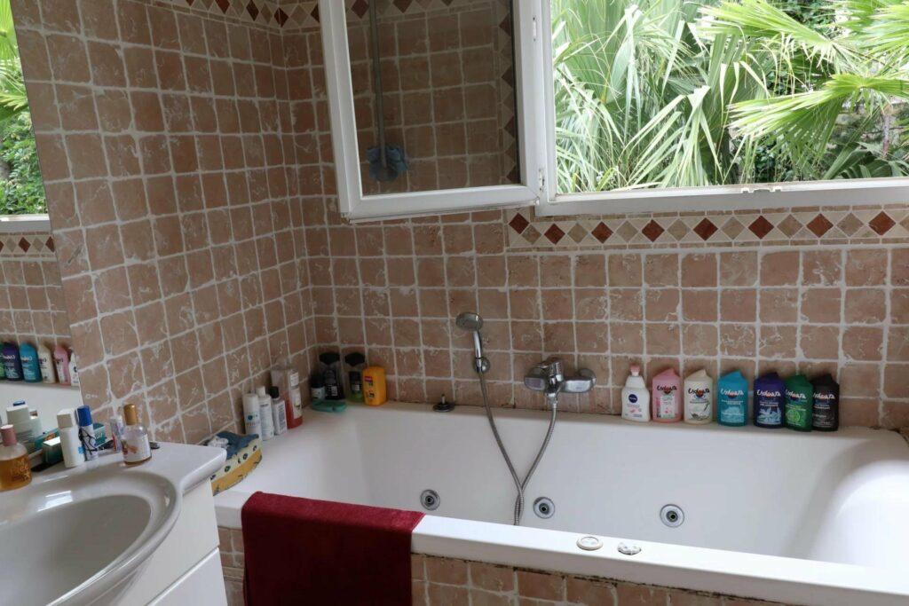 villa bathroom with bathtub and window to palm grove
