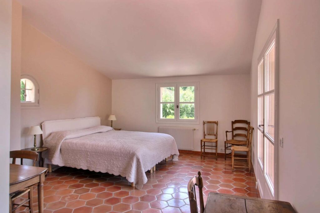 bedroom of opio house with red tile floors and white bedding