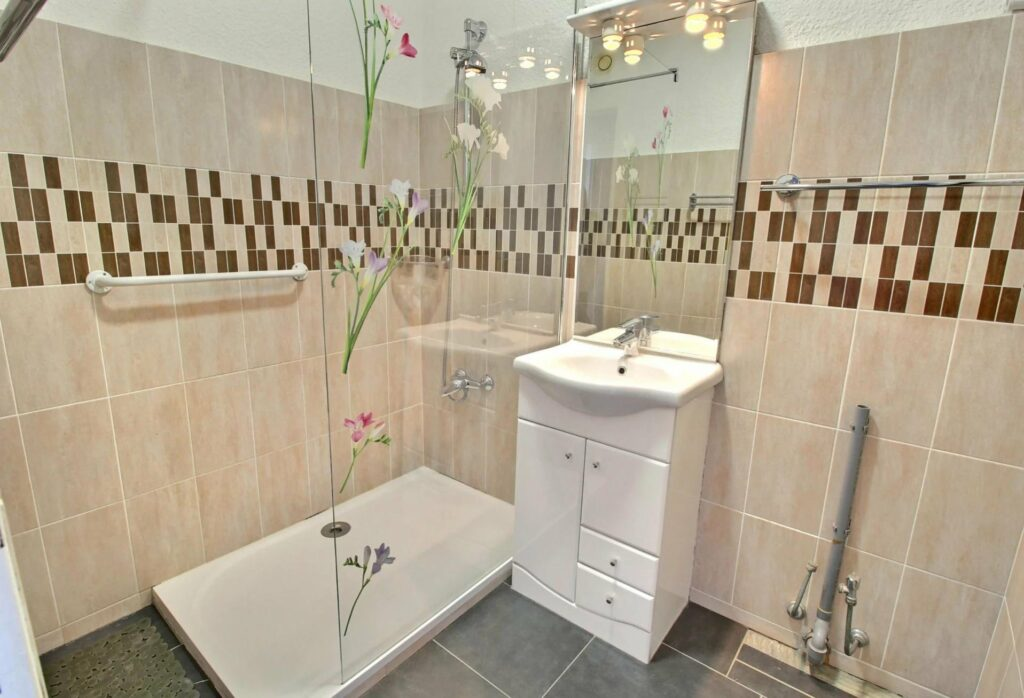bathroom with single sink and printed tile walls