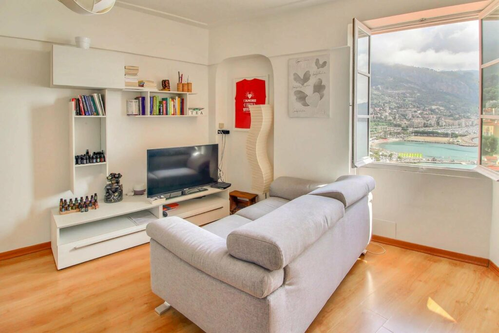 living room of apartment menton with grey couch sofa and window with sea view south france