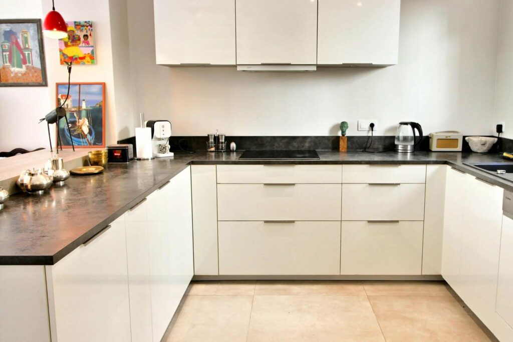 modern kitchen in house villefranche with white cabinets and dark granite counter tops