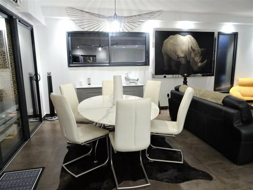 contemporary dining room with white cushioned chairs and black tile floors