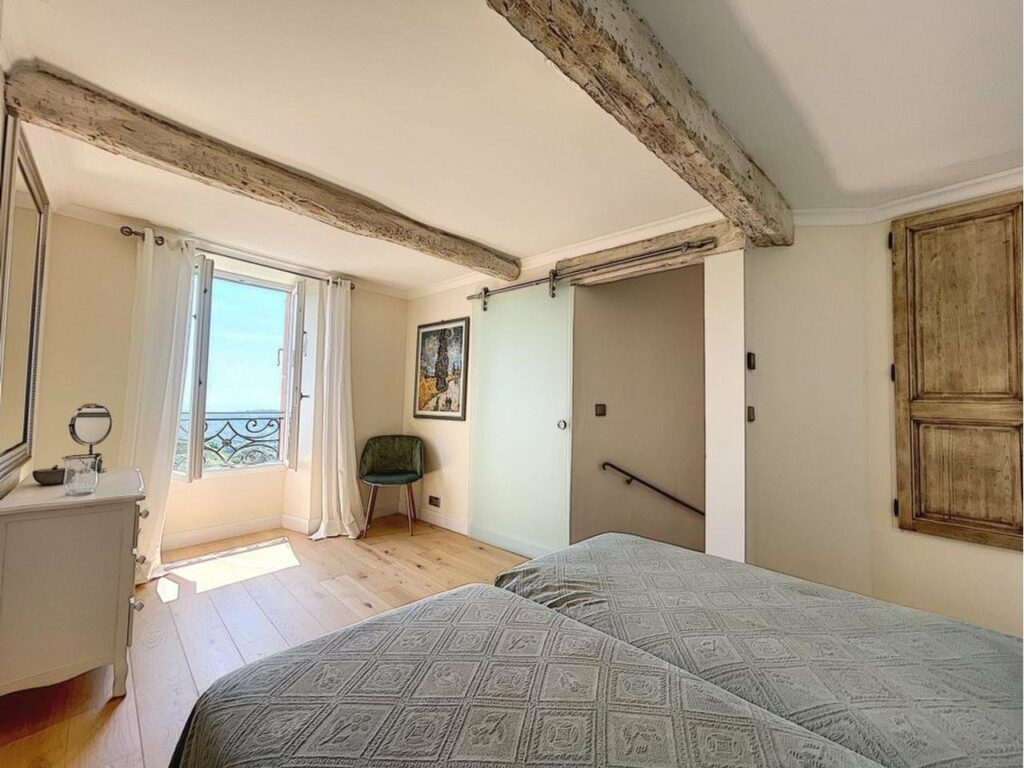 large upstairs bedroom with two single beds and exposed grey toned beams with large window sea view