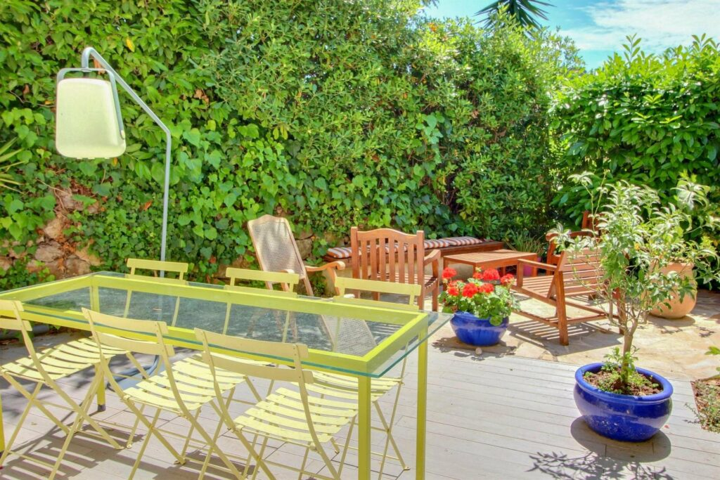 outdoor furniture in backyard garden of property in south france with large trees and green glass table